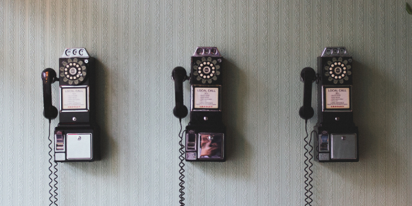 three rotary-dial pay phones on a wall